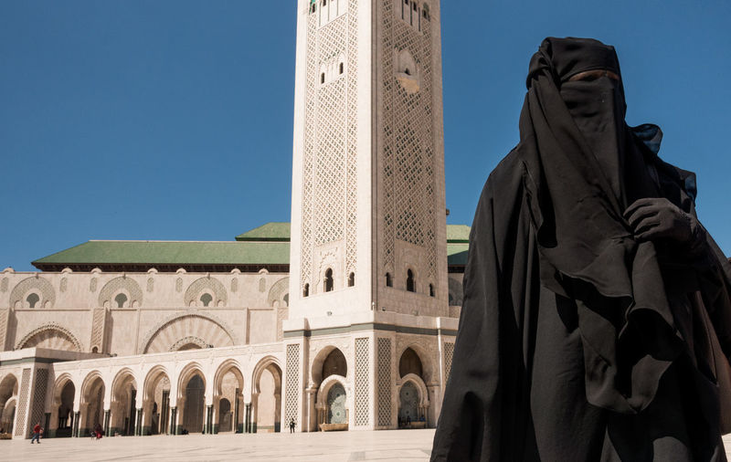 Casablanca mosque Hassan II and a muslim woman in black clothes and a burka covering her face Casablanca Casablanca Mosque Hassan II Mosque Woman Architecture Black Burka Building Building Exterior Built Structure Burka  City Day History Island Mosque Muslim Religion Tower Travel Travel Destinations First Eyeem Photo