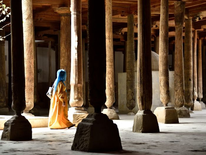 Woman walking by columns in building