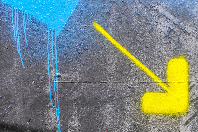 Yellow Wall - Building Feature Day No People Built Structure Architecture Textured  Paint Creativity Graffiti Wall Spray Paint Full Frame Outdoors Close-up Art And Craft Blue Communication Backgrounds Sign Concrete Graffiti Graffiti & Streetart Arrow Sign Arrow Symbol