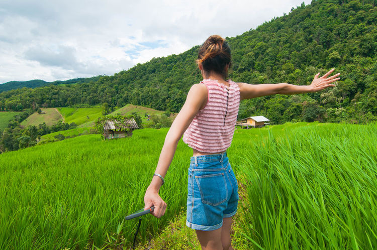 The Women who stand in rice terrace and breathe fresh air on the morning. Chaing Mai Beauty In Nature Casual Clothing Cereal Plant Cloud - Sky Day Field Grass Green Color Growth Landscape Nature One Person Outdoors People Plant Real People Rear View Rice Terraces Scenics Sky Standing Three Quarter Length Concept Young Adult