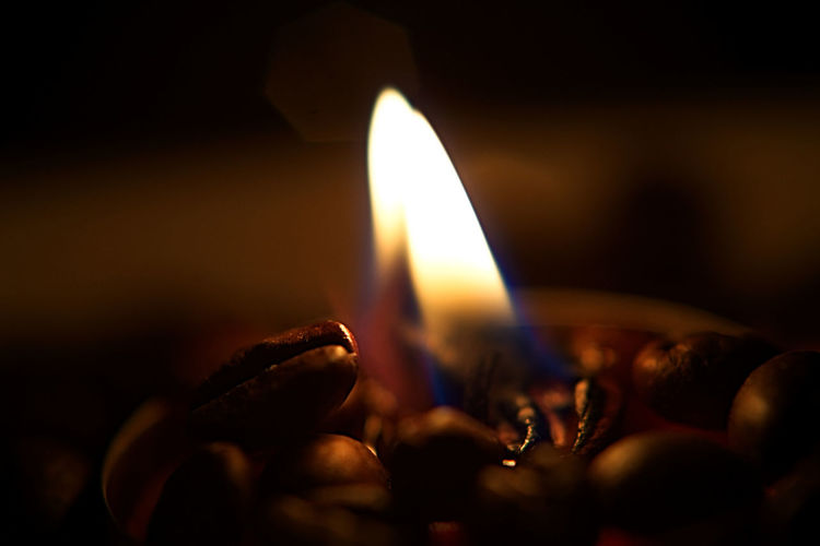 Close-up of burning candle on a coffee