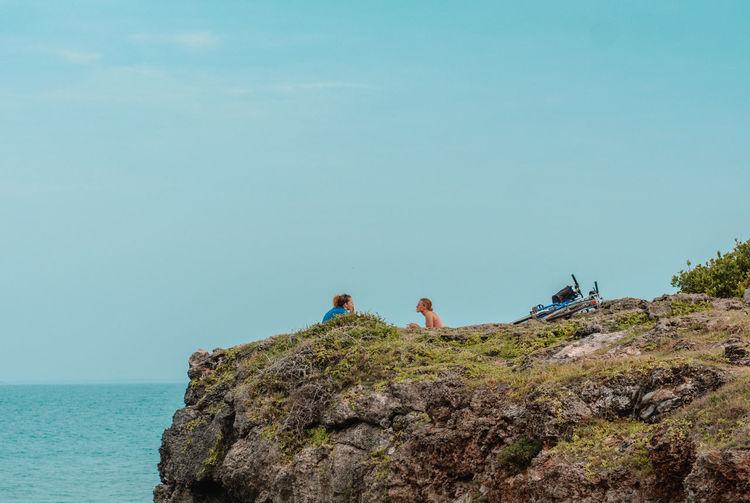 People on rock by sea against sky