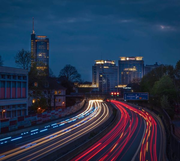 Light trails on road by buildings against sky at night