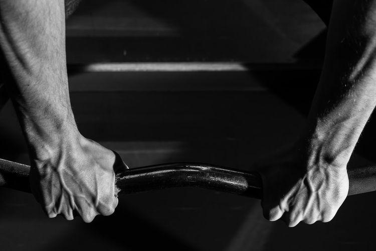 Cropped image of man gripping horizontal bar