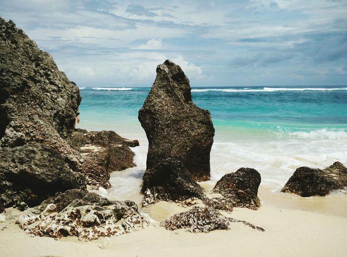 Rocks on beach against cloudy sky