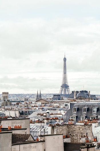 Eiffel tower and buildings in city against cloudy sky