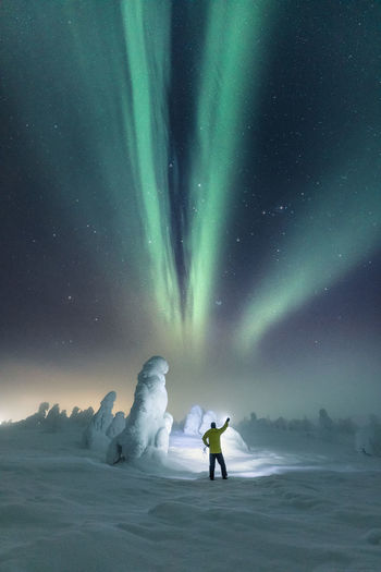 Rear View Of Man Standing On Snow Against Aurora Borealis