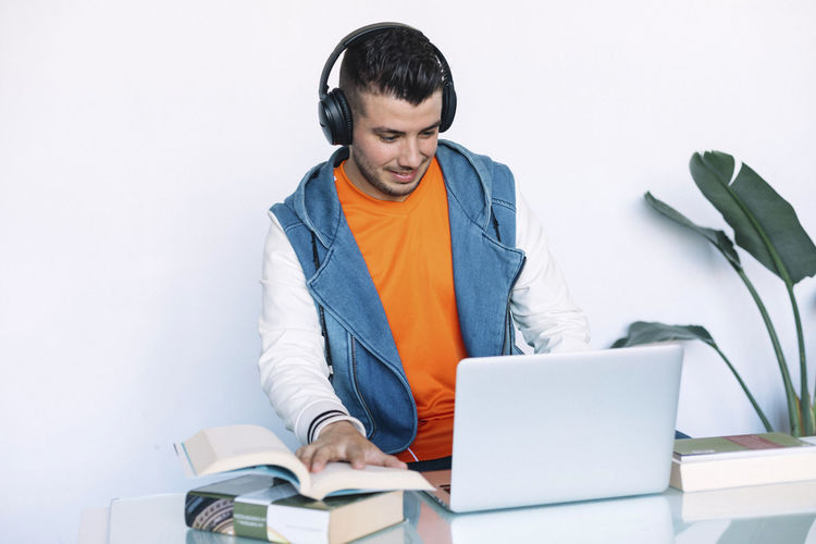 Man Sitting Computer Headphones Young Technology Adult Male Music Using Laptop Casual Working Listening Business People Internet Office Handsome Job Looking Worker Portrait Wireless Professional Indoors  Smiling Happy Workplace Work Beard Enjoying Cheerful Notebook Home Hipster Attractive One Freelance Successful Lifestyle One Person Front View Wireless Technology Book Men Publication Communication Real People Using Laptop