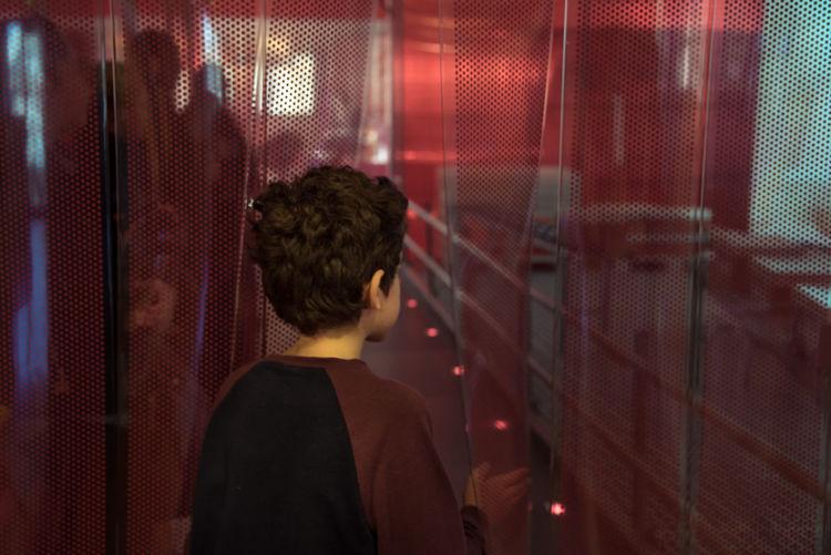 Rear view of boy standing in nightclub