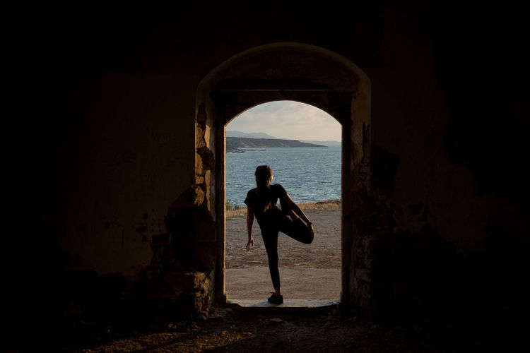 Woman exercising on doorway against sea during sunset