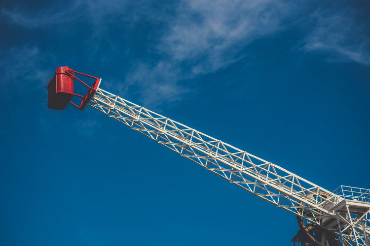 Low angle view of crane against blue sky