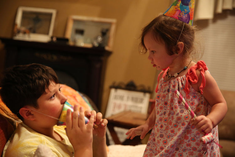 Girl looking at brother wearing party hat during birthday celebration