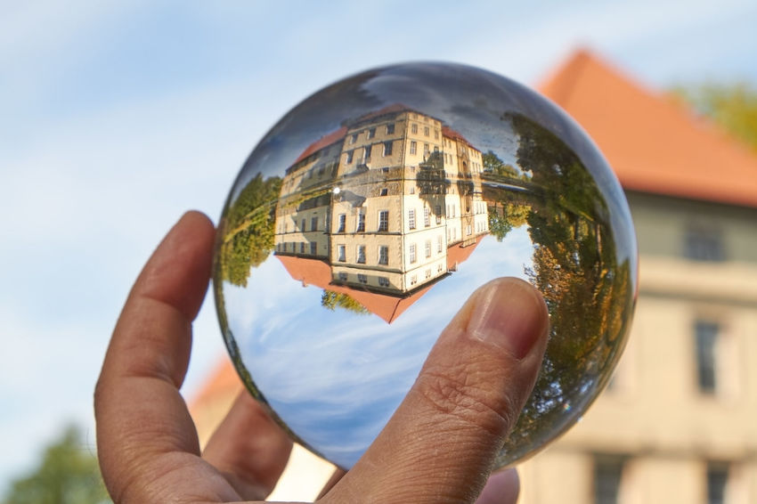 Water Castle Castle Architecture Ball Building Exterior Built Structure Close-up Day Finger Focus On Foreground Glass Glass - Material Hand Holding Human Body Part Human Hand Lifestyles Magic Nature One Person Outdoors Reflection Sky Sphere Transparent Unrecognizable Person Water Water Castle