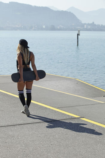 Rear view of woman carrying skateboard on road by sea