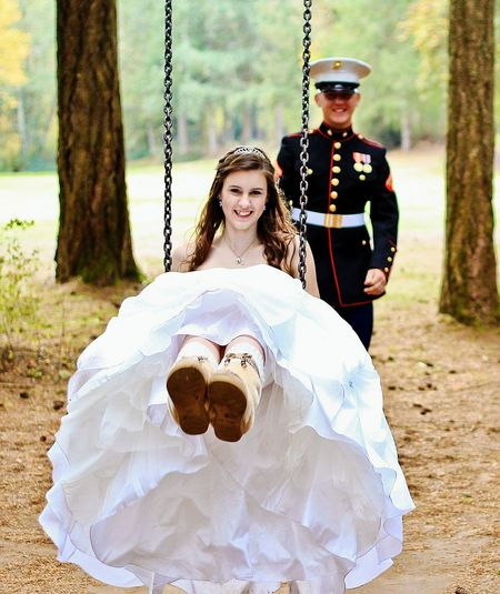 Portrait of beautiful bride swinging against navy officer