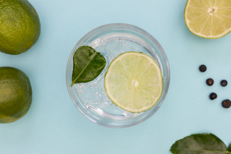 GIN Tonic Cocktail Drink Glass Ice Cold Blue Background Minimal Summer Top View Overhead Above Flat Lay Lime Green Lemon Cucumber Juniper Berries Alcohol SLICE Fruit Botanical Beverage Leaf Color Refreshment Mint Rhubarb Bubbles Sparkling