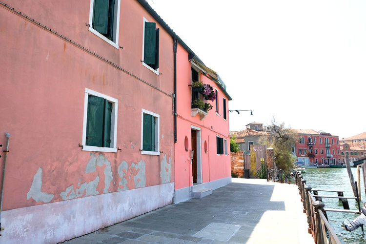 pink buildings along city streets Architecture Building Exterior Built Structure Building Day Outdoors Venice Italy Burano Murano City Summer Pink Color Pink Window Residential District Clear Sky Sky Nature House No People Footpath Copy Space Sunlight Wall - Building Feature Direction Wall Row House Alley Street