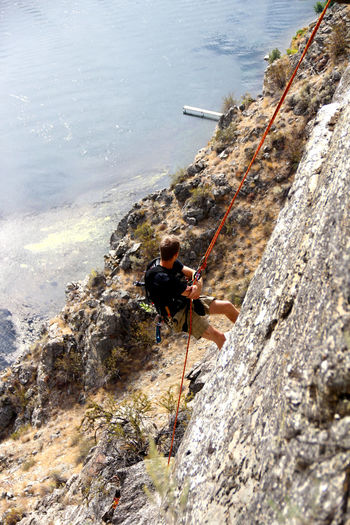High angle view of man rock climbing against sea