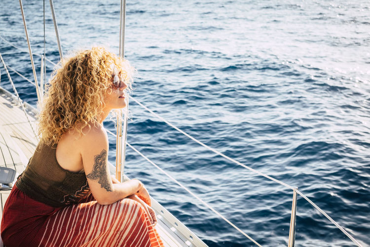Side view of woman sitting on sailboat in sea