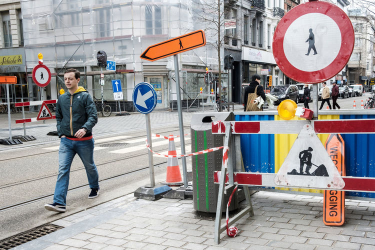 Pedestrian between signs Architecture Building Exterior Built Structure Casual Clothing City City Life Communication Day Full Length Guidance Human Representation Men Mode Of Transportation Outdoors People Real People Road Road Sign Sign Street Transportation Young Adult