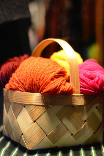 wool threads in a wooden hand work basket, set for knitting and needlework Wool Textile Basket Ball Of Wool Material Multi Colored Thread Spool Decoration Design Craft Fiber Handmade Handwork Hobby Needles Needlework Set Pink Orange Color Wood Wooden Yarn Clew Creativity
