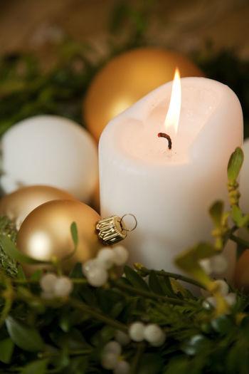 Close-up of illuminated candle and wreath