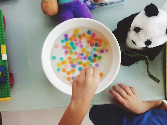 Cropped Image Of Boy Playing With Multi Colored Water Orbs