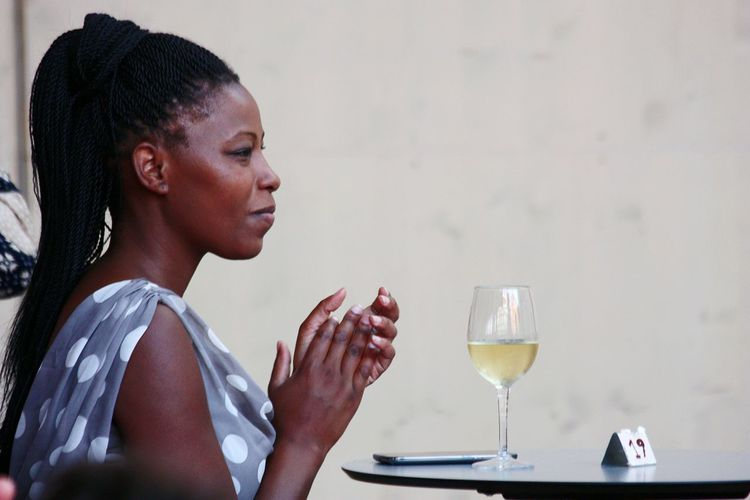 Side view of woman applauding while sitting at table against wall