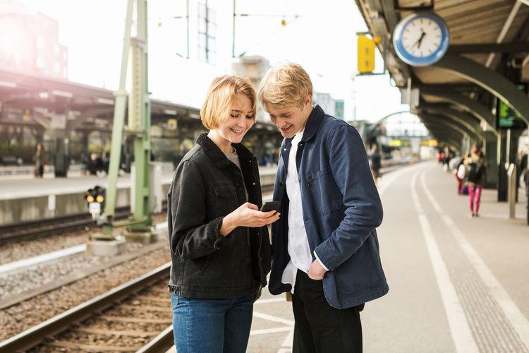 Friends standing on railroad station platform