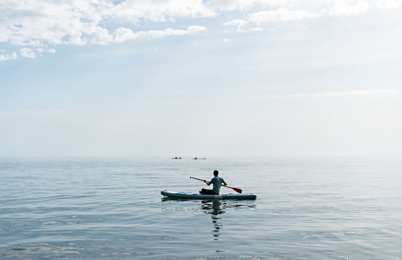 Young man from behind sitting on stand up paddle board on sea on sunny summer day, active lifestyle