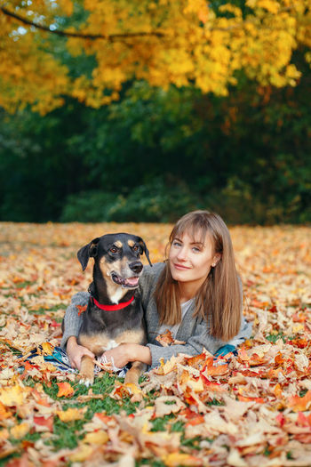 Portrait of woman with dog lying on dry leaves at park during autumn