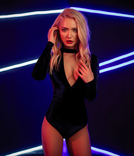 Fashion art photo of elegant blonde model in seductive wear with light neon colored club spotlights Adult Beautiful People Beautiful Woman Beauty Blond Hair Fashion Fashion Model Front View Hair Hairstyle Indoors  Long Hair Looking At Camera Neon Nightlife One Person Portrait Women Young Adult Young Women