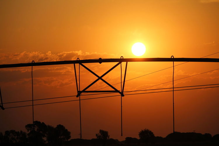 Silhouette electricity cables against sky during sunset