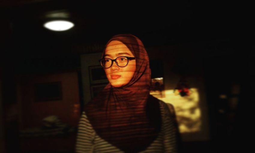Young woman wearing hijab looking away at home