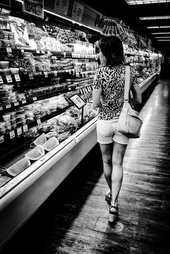 Full length rear view of woman standing at store