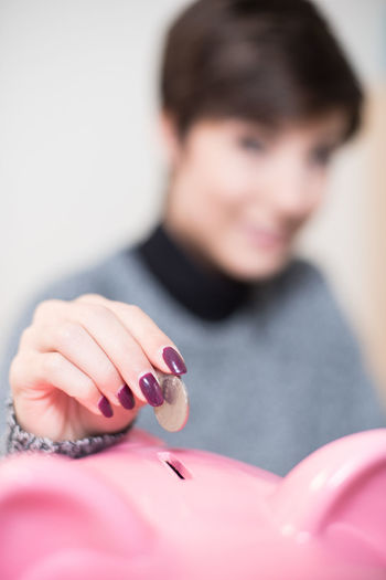 Close-Up Of Woman Putting Coin Into Piggy Bank