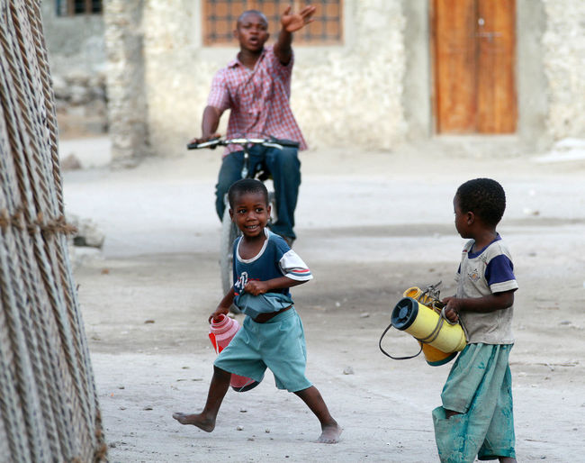 Zanzibar, Tanzania - February 18, 2008: Two unidentified African boy about 8 years old, go for water carrying the empty jars. black african children playing in the street fishing village Day Outdoors Africa Eastern Africa Fisherman People African Tanzania Zanzibar Africa Zanzibar_Tanzania Zanzibar Sand Child Childhood Males  Boys Men Full Length Innocence Togetherness Children Outdoor Games Outdoor Activities Outdoor Play Three People