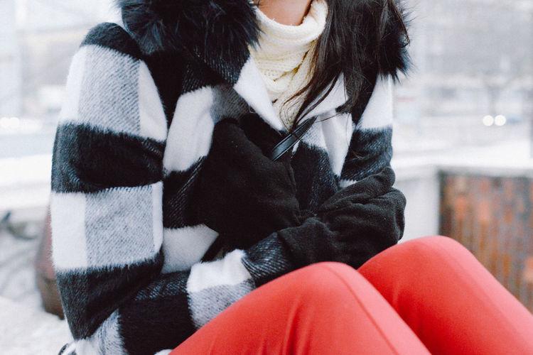 Woman sitting in city in winter