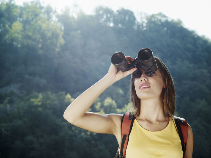 Portrait of young woman wearing sunglasses standing against mountain