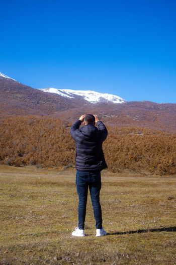 Rear view of man on mountain against clear sky