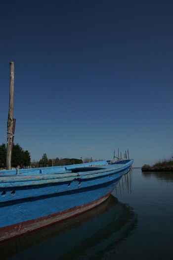 Boat moored in sea against clear blue sky