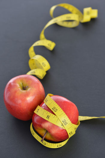 An apple with measuring rope Apple - Fruit Close-up Day Freshness Fruit Healthy Eating Healthy Lifestyle Indoors  Measuring Rope Measuring Tape No People Studio Shot Yellow