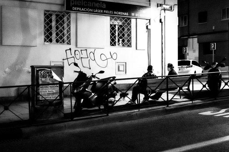 People on sidewalk against wall in city