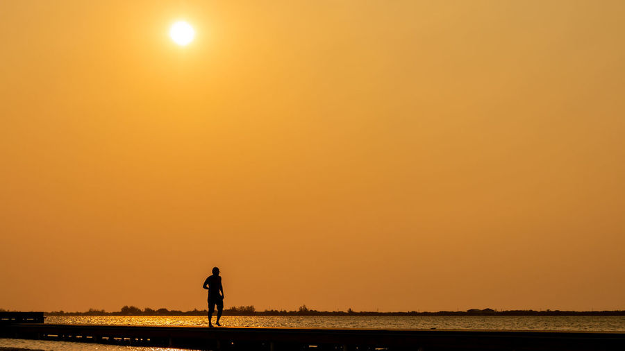 Silhouette man walking at beach against sky during sunset