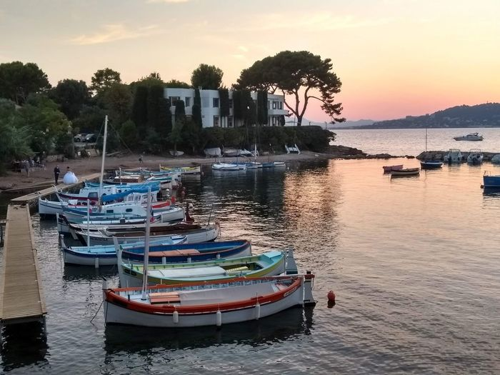 Boats moored in lake at sunset