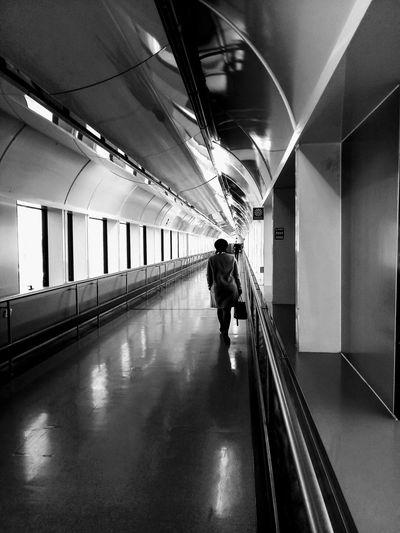 Rear view of woman walking in illuminated building corridor