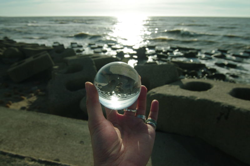 Midsection of person holding crystal ball in sea against sky