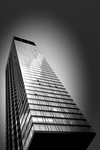 Low angle view of modern glass building against clear sky