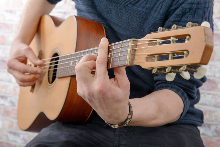 Musical Instrument String Instrument Music Guitar Playing Arts Culture And Entertainment One Person Midsection Leisure Activity Musical Equipment Real People Holding Plucking An Instrument Front View Human Hand Casual Clothing Skill  Musical Instrument String Hand Musician Acoustic Guitar Finger