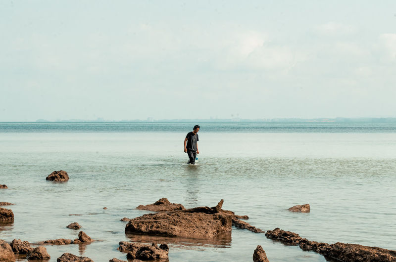 Man walking in the shallow water in beach